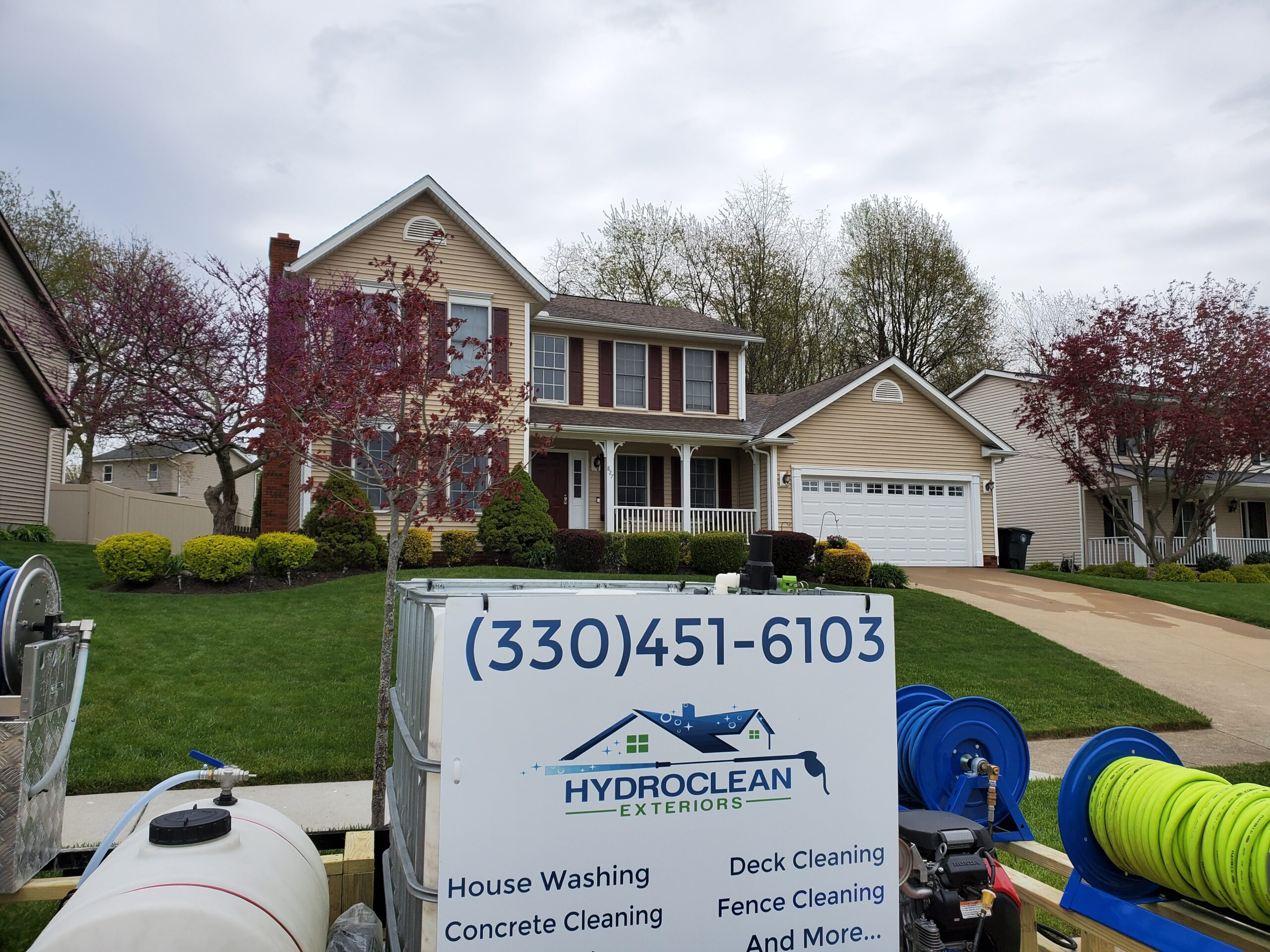 House with pressure washing trailer in front
